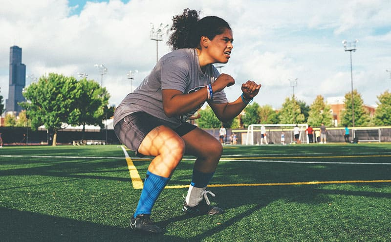 A woman doing squats on a sport field, unhindered by her shin pain thanks to the best compression sleeves.
