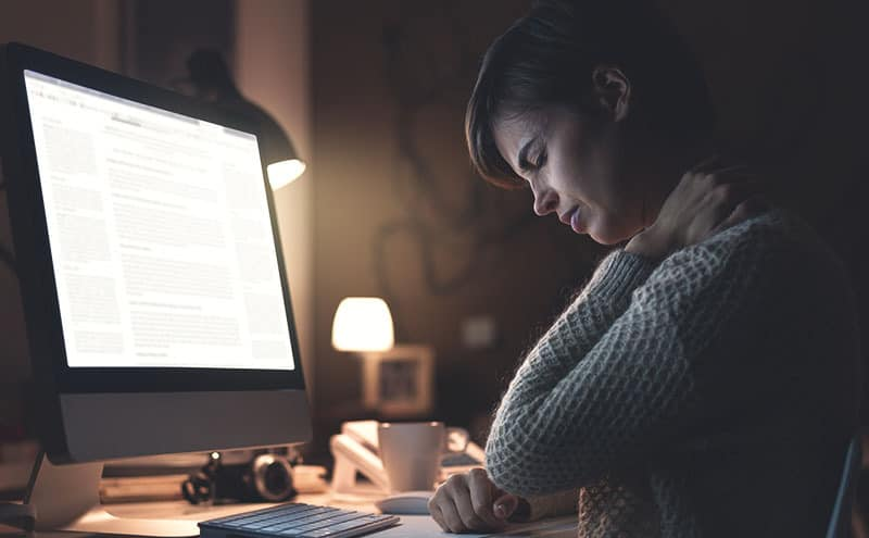 A woman with neck pain in an office at night in front of a computer considering buying one of the best neck braces.