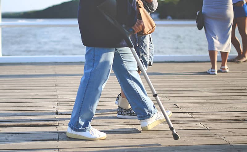 An adult walking with the best forearm crutches on a dock.