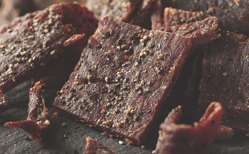 Black peppered beef jerky that is healthy for you on a dark surface.