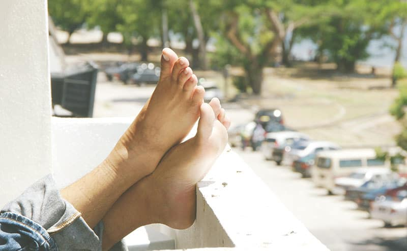 A person sitting on a balcony and putting her feet up, showing that they are quite healthy thanks to the best toe separators for painful foot conditions.